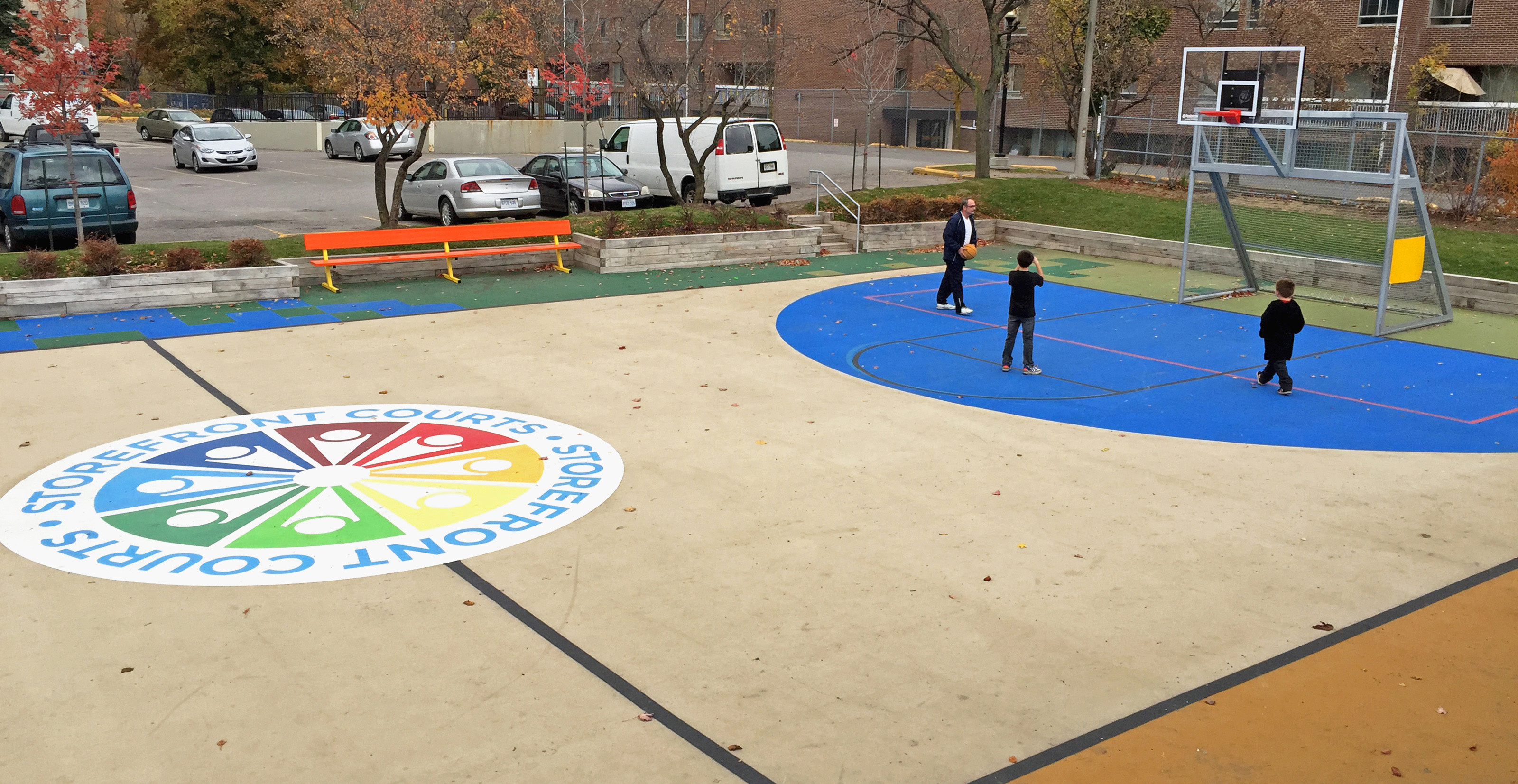 Court side view of 2 children and an adult playing basketball on the Storefront Courts.