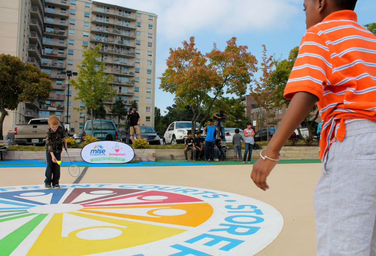 Two boys playing badminton on the East Scarborough Storefront court. They are standing on the centre colourful graphic.