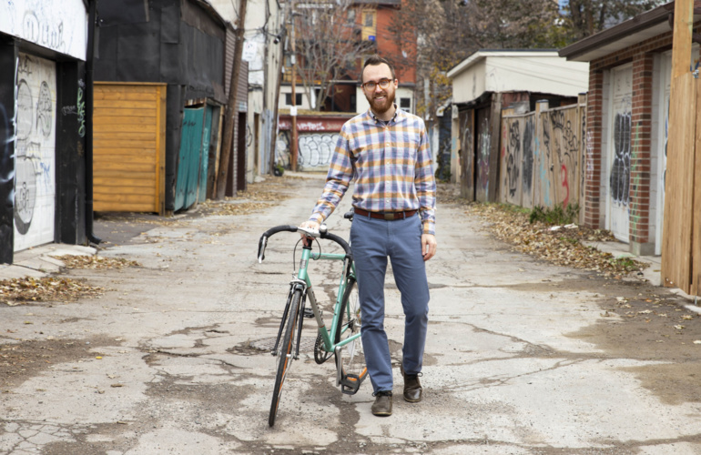 Team member Jay outside in a laneway standing next to his bike.