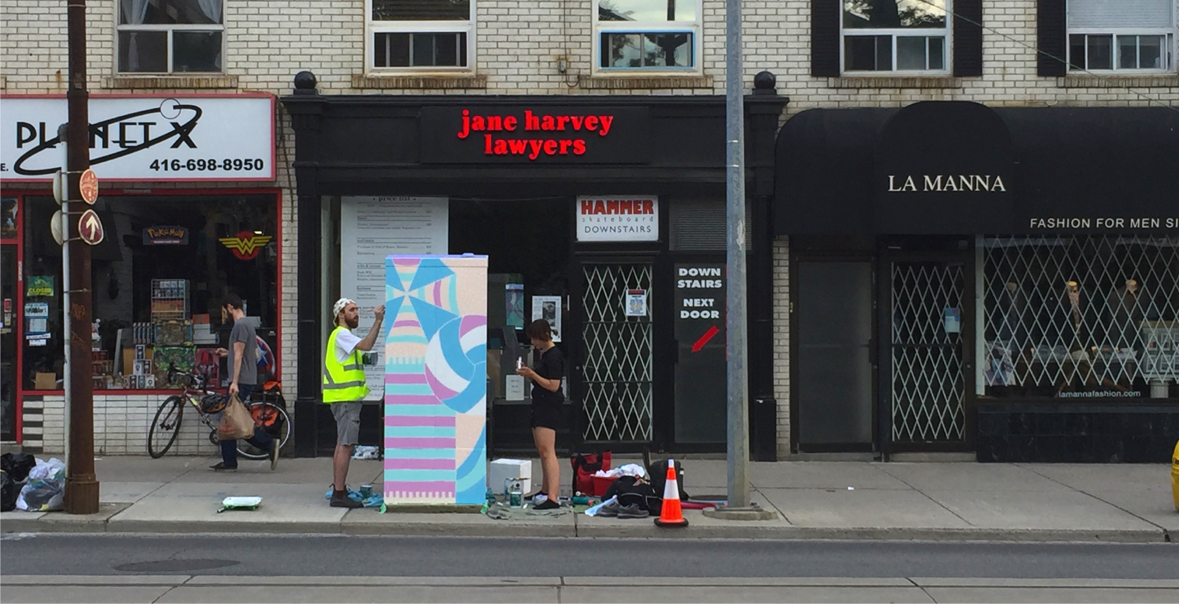 View from across the street of two studio members painting the traffic signal box.