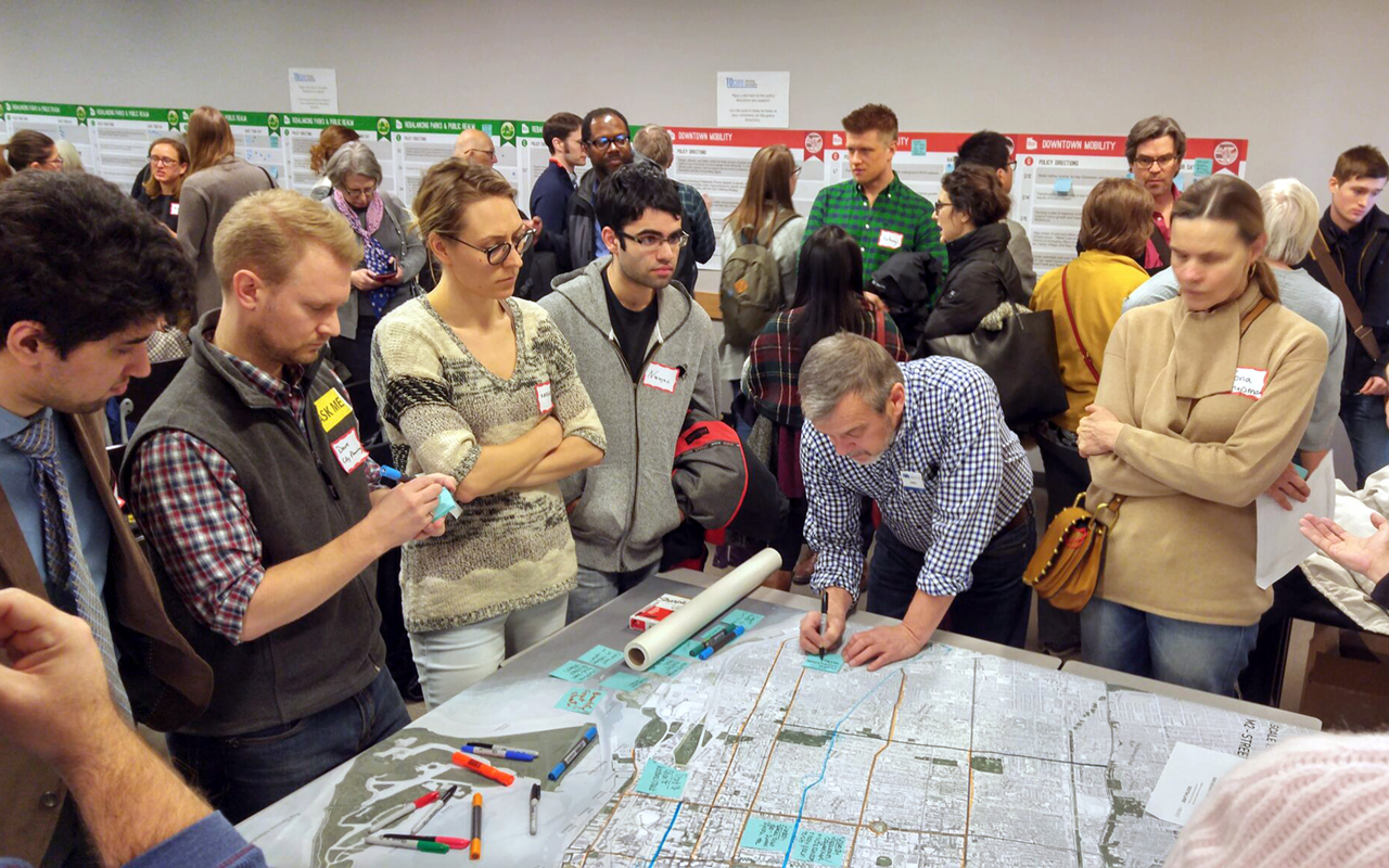Photo from a community consultation for TOcore with people standing at a table with a map of downtown Toronto.