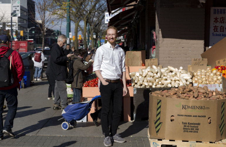Close up of team member Fraser outside in front of a market in Chinatown.